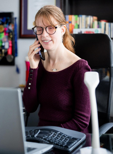 Elizabeth Mohler sitting at the computer talking on the on the telephone