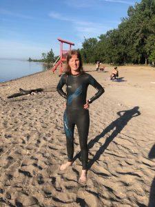 Elizabeth in wet suit on a beach